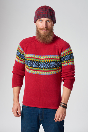 tog: Serious bearded hipster man in woolen sweater and a hat looking at camera, studio portrait over grey background Stock Photo