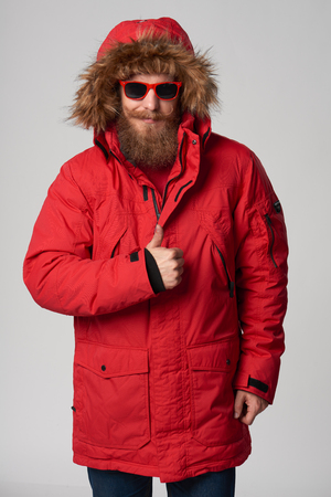 smiling bearded man in red winter jacket showing thumb up gesture, over grey background Stock Photo