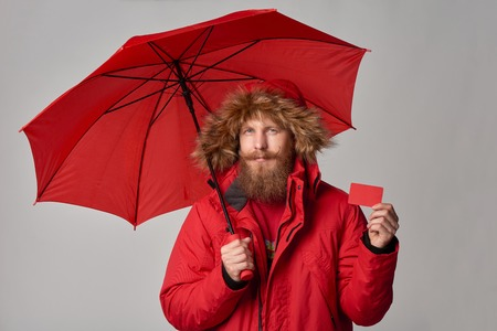 Man in red winter jacket standing under umbrella and showing blank credit card, over grey background Stock Photo