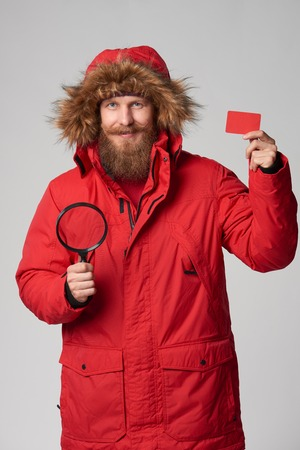 winter jacket: Search finance concept. Portrait of a man wearing red winter jacket with hood on showing blank credit card and holding magnifying glass, studio shot
