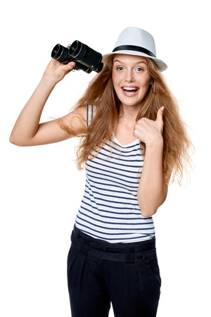 Happy emotional young beautiful teen female in striped tee and white straw fedora hat holding binoculars and looking at camera and gesturing thumb up, over white background Stock Photo