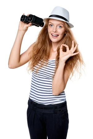 Happy emotional young beautiful teen female in striped tee and white straw fedora hat holding binoculars and looking at camera and gesturing OK, over white background Stock Photo