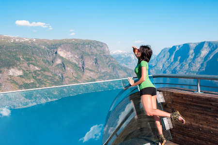 spectacular: Woman enjoying scenics from Stegastein Viewpoint in a summer sunny day, looking forward with hand on forehead Flam, Norway