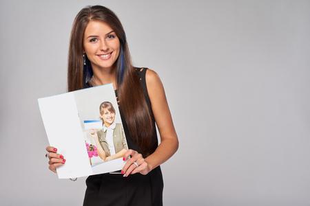 그녀의 사진으로 광고 브로셔를 보여주는 웃는 사업 여자 스톡 콘텐츠