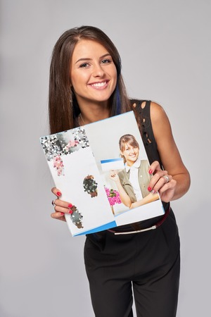 showing: Smiling business woman showing an advertising brochure with her photo