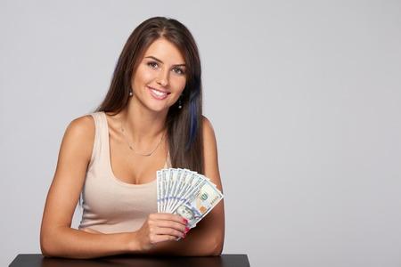 ganancias: Mujer con nosotros dinero del dólar en la mano sobre fondo gris, con copia espacio Foto de archivo