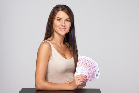 paper currency: Woman with euro money paper currency in hand over grey background, with copy space Stock Photo