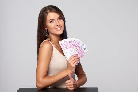 Woman with euro money paper currency in hand over grey background and gesturing thumb up