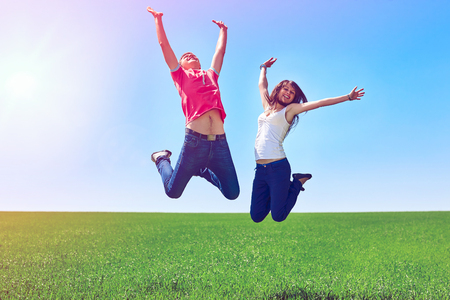 Happy couple jumping of joy in green field against blue sky