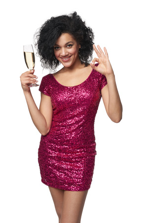 sequined: Party, drinks, holidays and celebration concept. Happy mixed race woman in sequined dress with glass of champagne gesturing OK hand sign Stock Photo