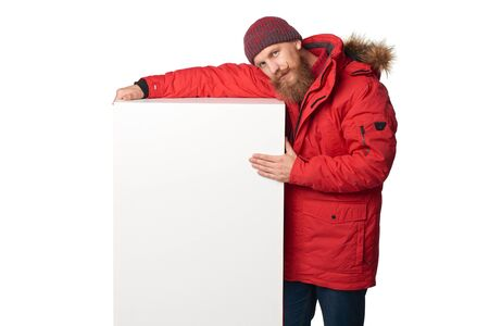 tog: Man wearing red winter jacket embracing big white box banner with copy space, isolated on white