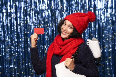 iceskates: Smiling young woman in red winter hat and scarf carrying a pair of ice skates and showing blank credit card over blue glittery background