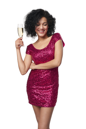 sequined: Party, drinks, holidays and celebration concept. Happy playful laughing mixed race woman in sequined dress with glass of champagne, looking down