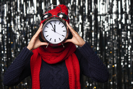 New Year eve concept. Woman in winter hat and scarf holding with big alarm clock counting to midnight covering her face.
