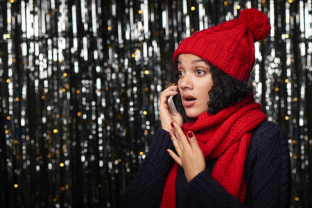 gasping: Surprised woman warm winter clothing talking on cell phone Stock Photo
