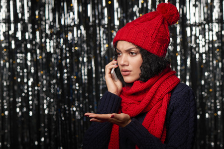 Displeased woman warm winter clothing talking on cell phone