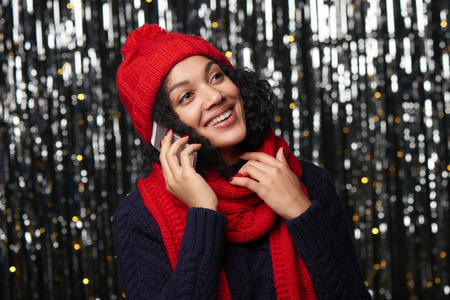 Happy smiling woman in warm winter clothing talking on cell phone looking away