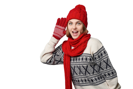 Happy emotional young woman in winter warm clothing listening gossip with palm at ear