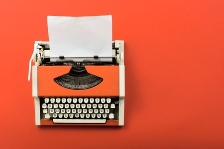 Top view of red vintage typewriter with white blank paper sheet on table