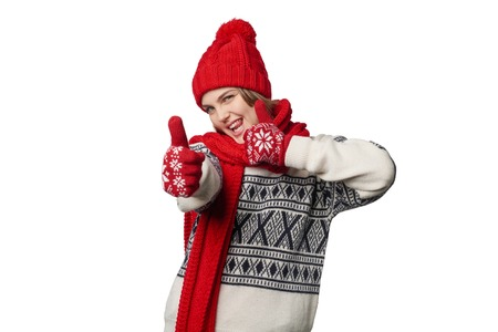 Excited winter warm clothing girl giving double thumb up, showing playful tongue, over white background Stock Photo
