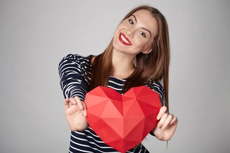 outstretching: Smiling woman holding red polygonal paper heart shape