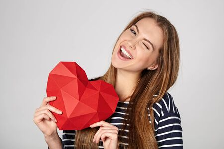 playful: Smiling woman holding red polygonal paper heart shape