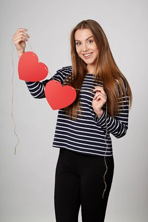 Smiling woman holding garland of two red paper hearts Stock Photo