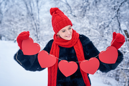 looking for love: Love and valentines day concept. Smiling woman holding garland of five red paper hearts shape - blank copy space for letters or text, looking down at hearts over winter landscape