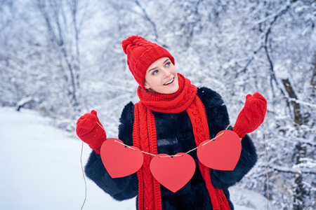 looking for love: Love and valentines day concept. Smiling woman holding garland of three red paper hearts shape - blank copy space for letters or text, looking up over winter landscape
