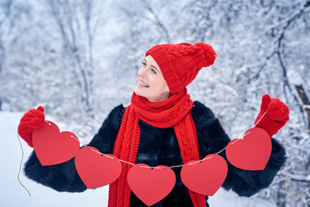 looking for love: Love and valentines day concept. Smiling woman holding garland of five red paper hearts shape - blank copy space for letters or text, looking up over winter landscape Stock Photo