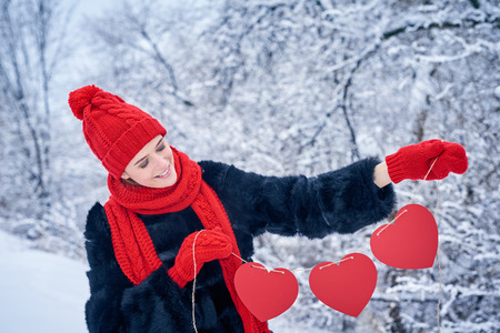 looking for love: Love and valentines day concept. Smiling woman holding garland of three red paper hearts shape - blank copy space for letters or text, looking down at hearts over winter landscape Stock Photo