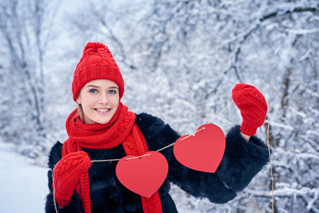 looking for love: Love and valentines day concept. Smiling woman holding garland of two red paper hearts shape - blank copy space for letters or text, looking at camera over winter landscape