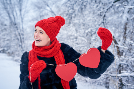 looking for love: Love and valentines day concept. Happy laughing woman holding garland of two red paper hearts shape - blank copy space for letters or text, looking away over winter landscape