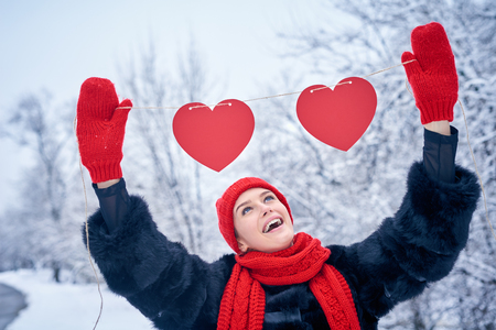 Love and valentines day concept. Happy excited woman holding garland of two red paper hearts shape - blank copy space for letters or text over winter landscape