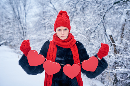 Love and valentines day concept. Discontent sullen woman holding garland of four red paper hearts shape - blank copy space for letters or text, looking at camera over winter landscape Stock Photo
