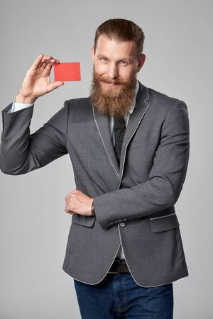 Hipster business man with beard and mustashes in suit standing over grey background holding credit card Stock Photo