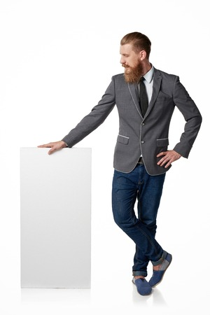 Hipster man with beard and mustashes standing in full length with blank banner looking down at it