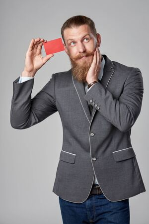 surprises: Surprised hipster business man with beard and mustashes in suit standing over grey background showing blank credit card looking up in amazement with hand on cheek.