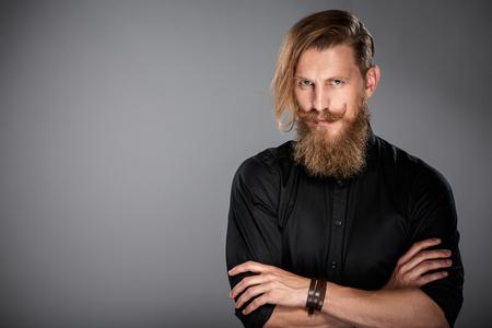 ひげと灰色の背景上、カメラ見つめて黒いシャツを着て mustashes 流行に敏感な人のポートレート、クローズ アップ