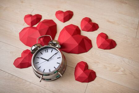 Closeup of big alarm clock with many red polygonal paper heart shapes over wooden bachground