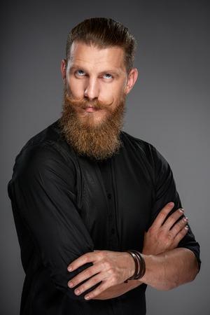 Porträt von schweren Hipster Mann mit Bart und mustashes stehend mit gefalteten Händen Nachschlagen Standard-Bild