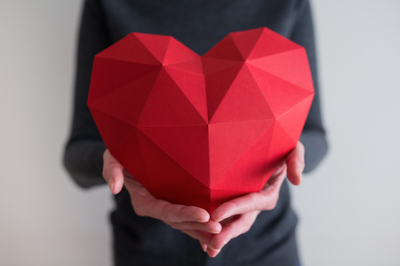 Woman showing red polygonal paper heart shape, cropped image