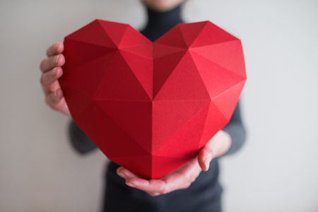 outstretching: Woman showing red polygonal paper heart shape, cropped image