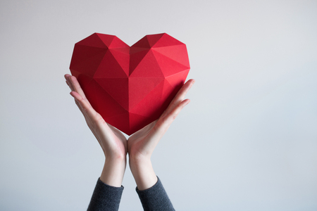 Two female hands holding red polygonal paper heart shape Standard-Bild