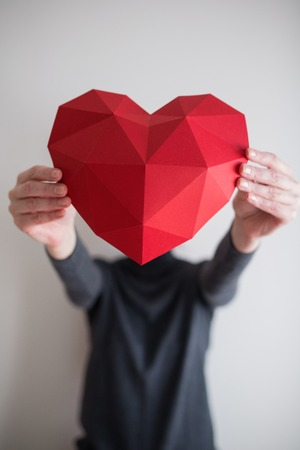 outstretching: Woman outstretching red polygonal paper heart shape covering her face. Shallow depth of field Stock Photo