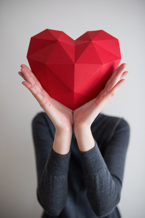 outstretching: Woman holding red polygonal paper heart shape covering her face. Shallow depth of field Stock Photo