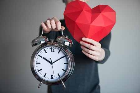 outstretching: Woman showing red polygonal paper heart shape and big alarm clock, cropped image