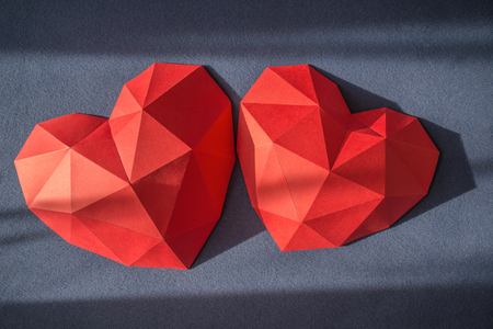 Two red polygonal paper heart shape over grey background with sun beams, top view