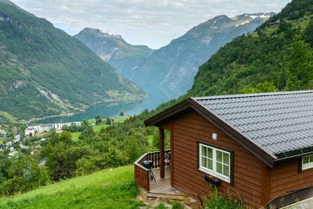 Beautiful view at fiord in a summer day with wooden cabin at foreground, Norway Stock Photo