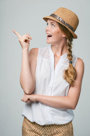 blank space: Happy surprised woman wearing summer straw fedora hat pointing finger to the side at blank copy space Stock Photo